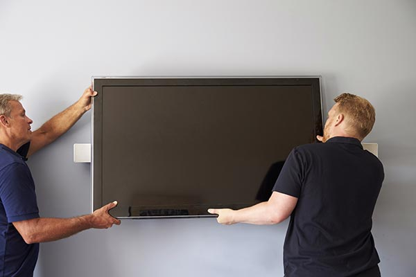 two men installing a tv on a wall mount
